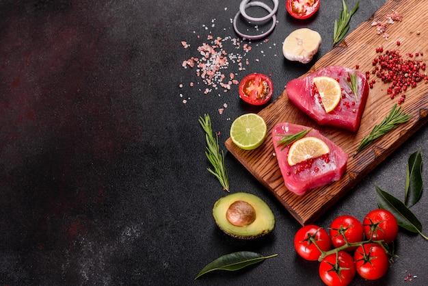 Bistecche di filetto di tonno fresco con spezie ed erbe aromatiche su una tavola nera
