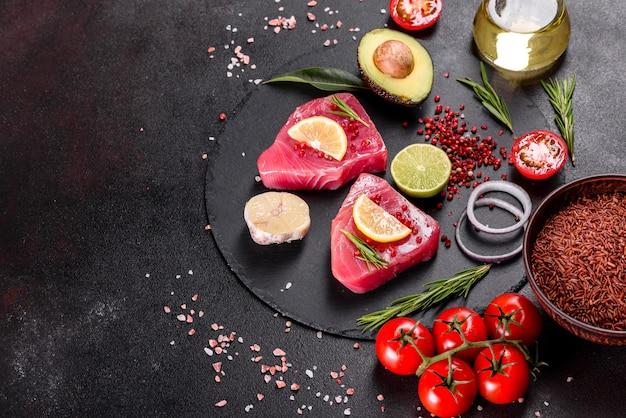 Bistecche di filetto di tonno fresco con spezie ed erbe aromatiche su fondo nero.