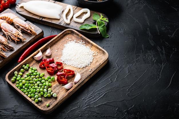 Ingredienti freschi della paella cruda con gamberoni, cozze e calamari su sfondo nero con texture con spazio per il testo