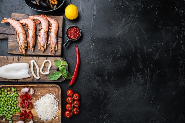 Ingredienti freschi per paella crudi con gamberoni, cozze e calamari su sfondo nero con texture