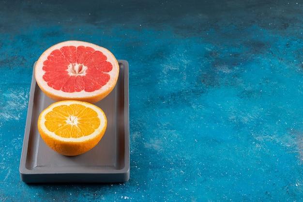 Vari frutti affettati freschi posti sulla superficie blu