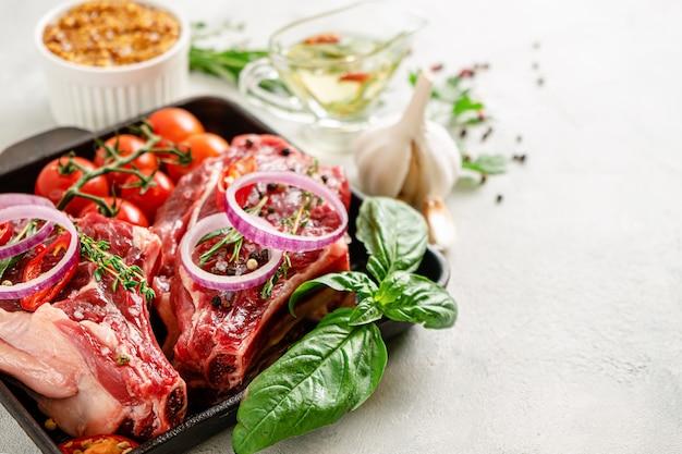 Bistecche fresche di osso di vitello con verdure, erbe e spezie su sfondo concreto