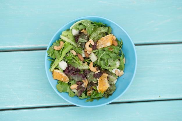 Insalata vegana fresca sulla tavola di legno blu, vista a volo d'uccello. colpo dall'alto