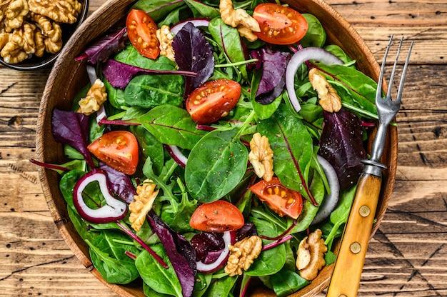 Insalata verde di verdure fresche con foglie di mangold, bietole, spinaci, rucola e noci. fondo in legno. vista dall'alto.
