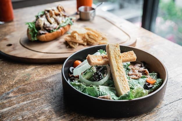 Un piatto di insalata di verdure fresche su un piatto nero con uno sfondo di hot dog e griglia di patate fritte
