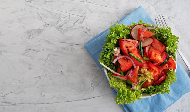 Insalata di verdure fresche in una tazza bianca su un tovagliolo blu. vista dall'alto