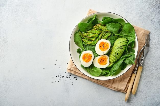 Insalata di verdure fresche con avocado asparagi uova sgualcite semi di sesamo nero e spinaci su piatto