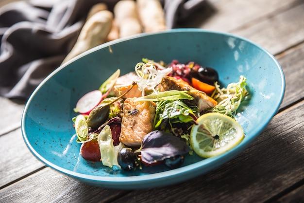 Insalata di verdure fresche con salmone arrosto olio d'oliva e baguette.