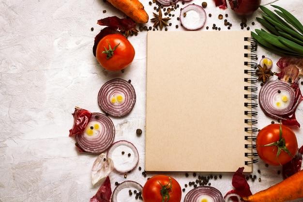 Verdure fresche intorno al blocco note per ricette alimentari su uno sfondo chiaro. concetto di cucina, vegetarismo e alimentazione sana