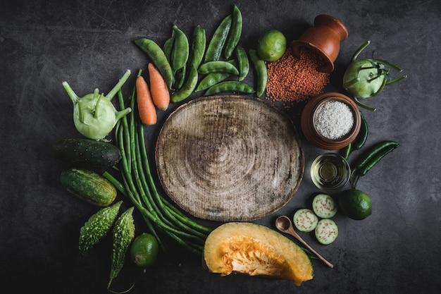 Verdura fresca su un tavolo nero con spazio per un messaggio nel mezzo