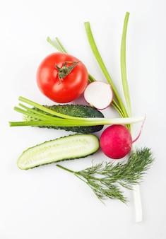 Verdure fresche sulla tavola, su uno sfondo bianco