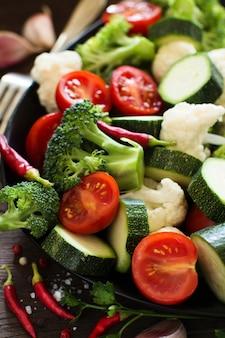 Verdure fresche si chiudono su un tavolo di legno