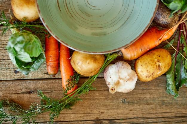 Verdure fresche per cucinare la zuppa intorno a un piatto vuoto verde rotondo su uno sfondo di legno di un tavolo dall'alto, stile di vita sano e concetto di cibo, cibo vegetariano e biologico.