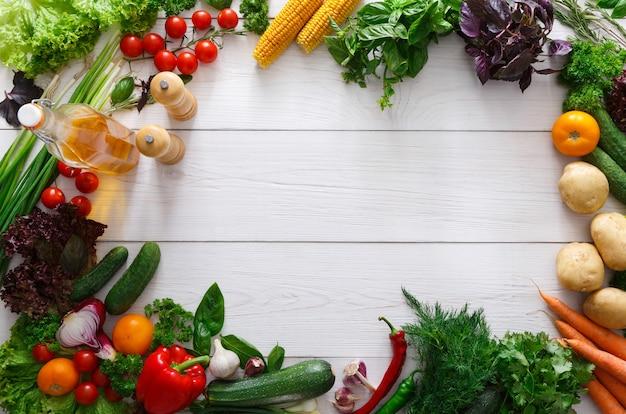 Cornice di verdure fresche su legno bianco con spazio di copia