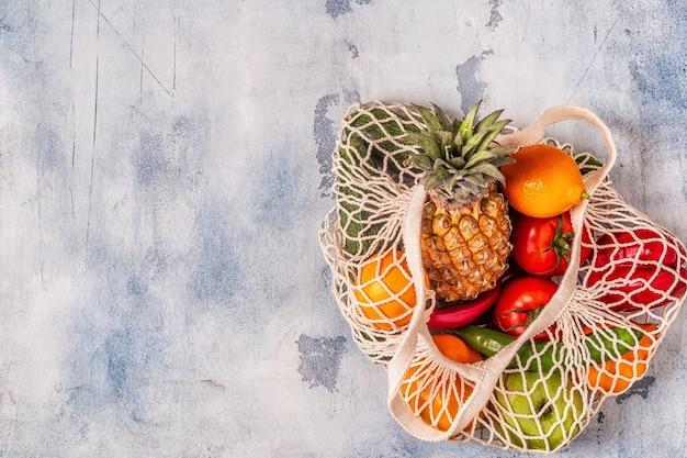 Verdure fresche e frutta in maglia di borsa, vista dall'alto.