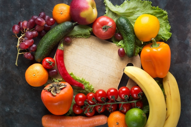 Verdure fresche e frutta su uno sfondo nero. vitamine e minerali. vista dall'alto. fai spazio per il tuo testo.