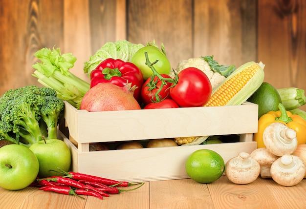 Verdure fresche e frutta in una scatola su uno sfondo di legno