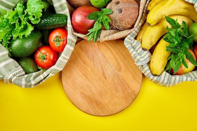 Verdure fresche e frutta in sacchetti di cotone eco attorno al tagliere sul tavolo in cucina