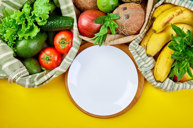 Verdura fresca e frutta in sacchetti di cotone eco intorno al piatto sul tavolo
