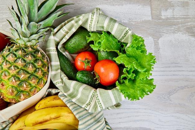 Verdura fresca e frutta in sacchetti di cotone eco sul tavolo in cucina.