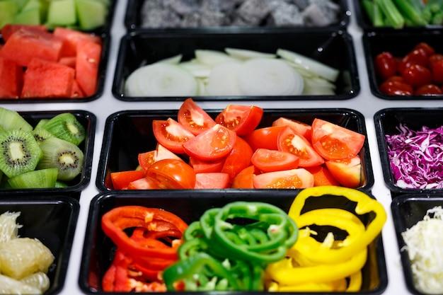 Verdure e frutta fresche affettate al buffet del salad bar