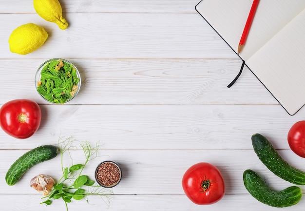 Verdure fresche, frutta e spezie con libro aperto sul tavolo bianco