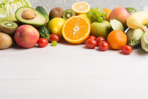 Verdura fresca e frutta sopra fondo di legno bianco
