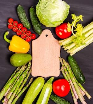 Verdure fresche per mangiare sano intorno a un tagliere su sfondo nero. raccolto stagionale primaverile. lay piatto, copia spazio. vista dall'alto. orientamento verticale