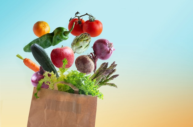 Verdure fresche in sacco di carta riciclabile isolato dallo sfondo