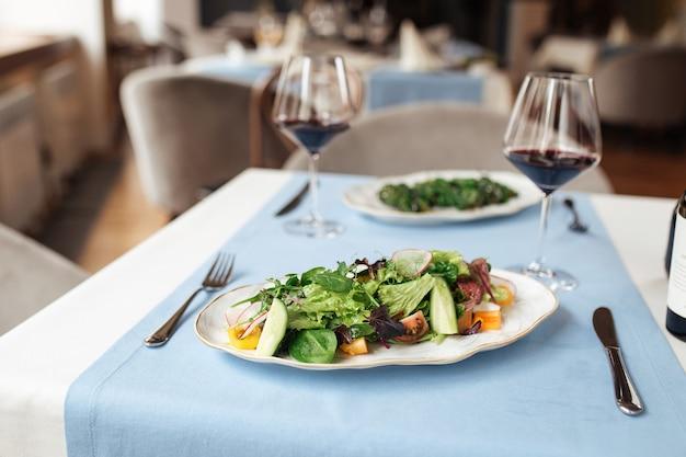 Insalata di verdure fresche sul tavolo del ristorante servito con bicchieri di vino rosso