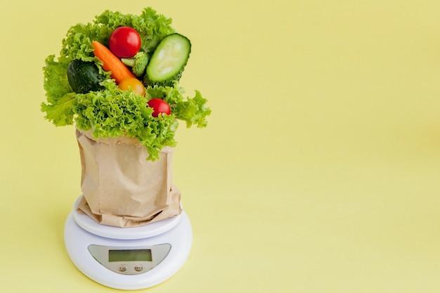 Verdure fresche su scale su sfondo giallo. vegan e concetto sano.