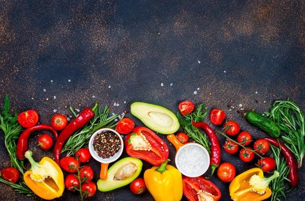 Verdure fresche, spezie, erbe e ingredienti sani su sfondo scuro vista dall'alto