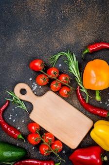 Verdure fresche spezie erbe ingredienti per una cucina sana o insalata su sfondo rustico scuro con spazio per il testo. vista dall'alto