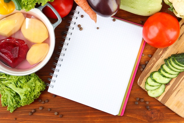 Verdure fresche e spezie e carta per appunti, su superficie in legno