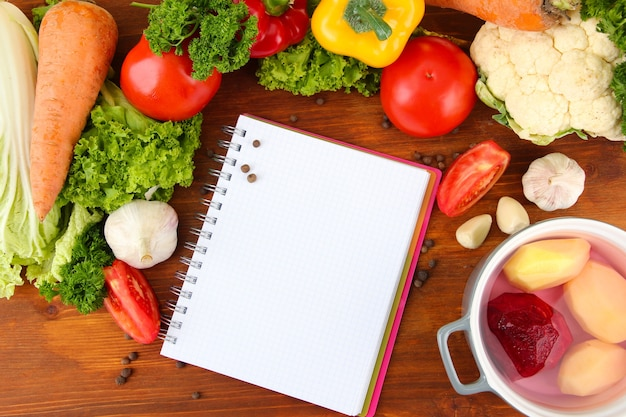 Verdure fresche e spezie e carta per appunti su tavola di legno