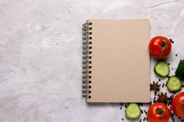Verdure fresche, pomodori, cetrioli, spezie, blocco note per ricette alimentari su sfondo chiaro. concetto di cucina, vegetarismo e alimentazione sana