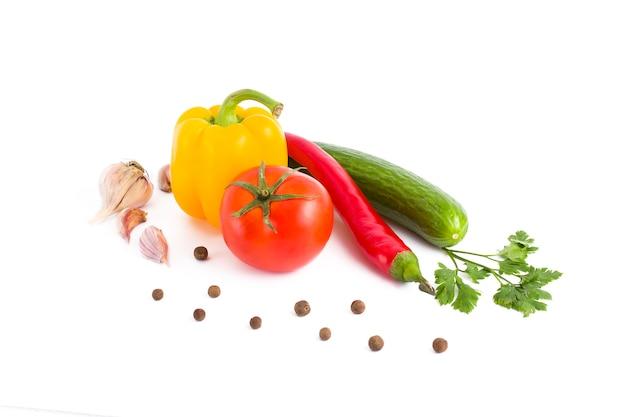 Verdure fresche su sfondo bianco peperone giallo, cetriolo verde, pomodoro rosso e pepe amaro su sfondo bianco.