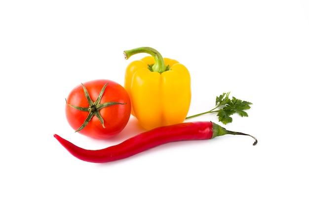 Verdure fresche su sfondo bianco peperone giallo, pomodoro rosso e pepe amaro su sfondo bianco.