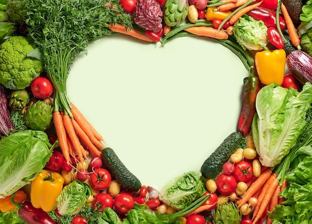Verdure fresche con spazio copia a forma di cuore, concetto di cibo sano