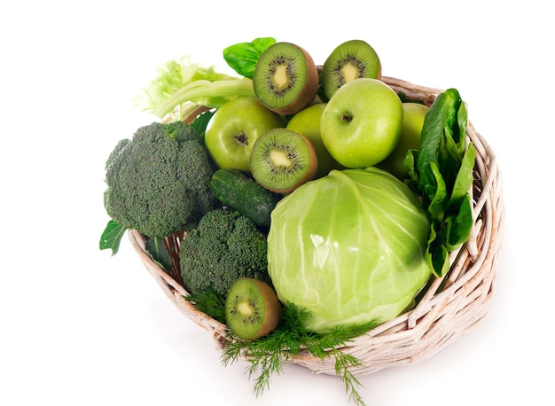Verdure fresche con foglie - broccoli, kiwi, sedano, spinaci, cavoli, uva e mela isolati su sfondo bianco