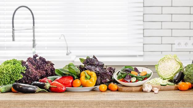 Verdure fresche su un tavolo di legno contro lo spazio di un interno di una cucina moderna.