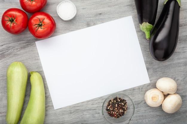 Verdure fresche sulla tavola di legno con carta bianca