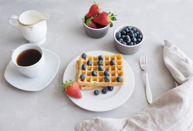 Waffle freschi viennesi o belgi con fragole e mirtilli e una tazza di caffè nero sul tavolo.