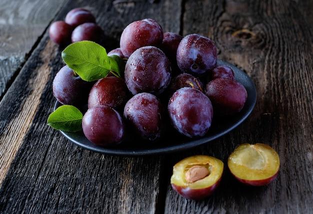 Prugne viola fresche al fondo di legno scuro della tavola