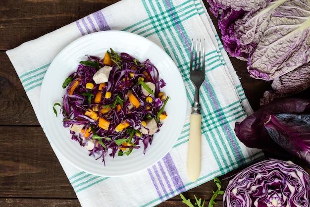 Insalata fresca di fitness vitaminico di cavolo rosso, peperoni, mais, rucola. diete vegane. la vista dall'alto