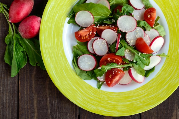 Insalata fitness vitaminica fresca con ravanello, rucola e sesamo. la vista dall'alto.