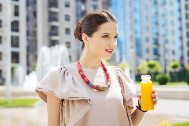 Vitamine fresche. piacevole bella donna che tiene una bottiglia con succo mentre lo beve