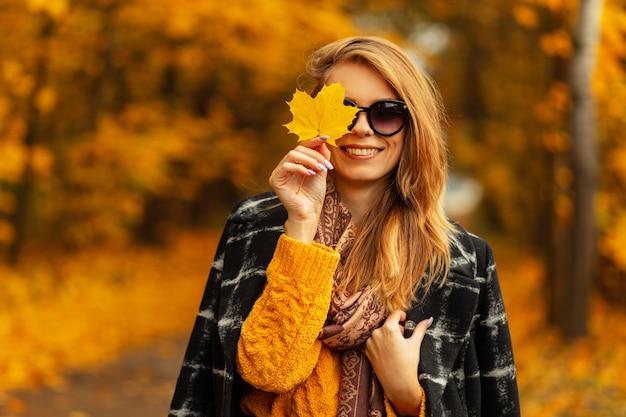 Ritratto di moda fresca di una giovane donna con labbra sexy in eleganti occhiali da sole rotondi e cappello di paglia poco elegante in bellissimo abito a righe. modello di moda ragazza attraente all'aperto. abiti estivi alla moda
