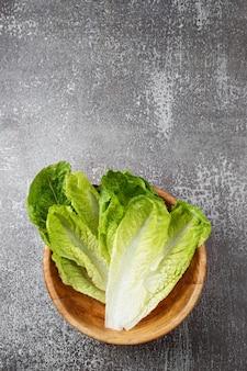 Insalata verde fresca lavata in una ciotola di legno pronta per la cottura. ingredienti per cucinare, dieta vegetariana, alimentazione sana. vista dall'alto, spazio per il testo.