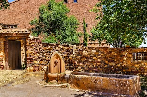 Fontana di acqua dolce all'ingresso di una vecchia casa in pietra.
